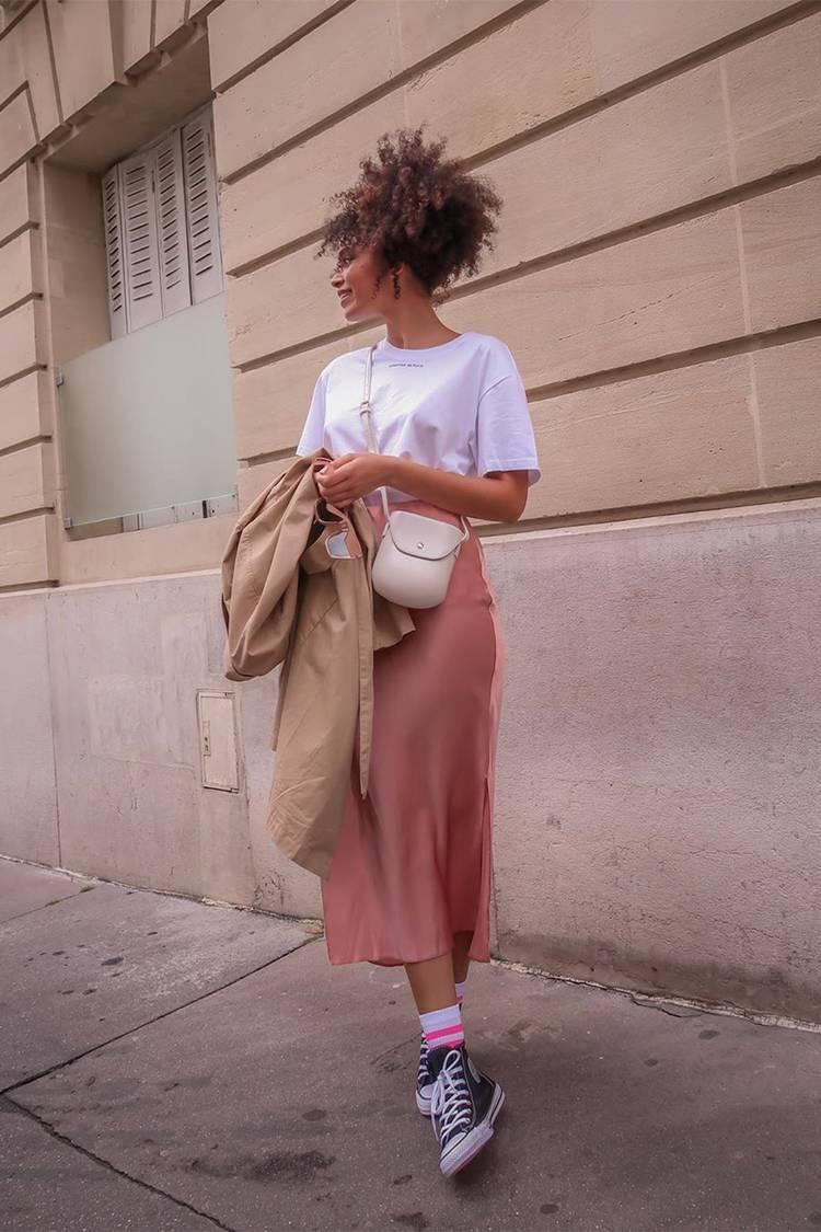 Девушка в розовой шелковой юбке, белая футболка и черные кеды