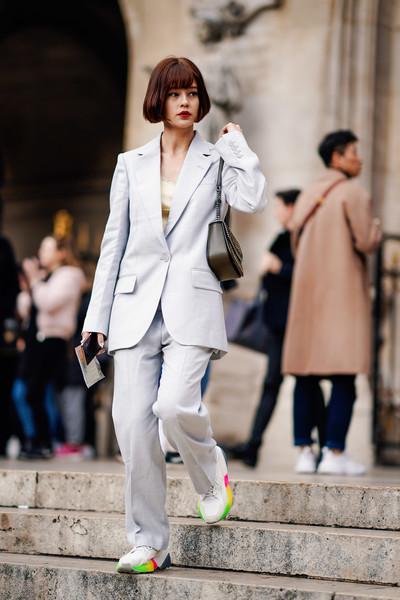 Девушка в сером костюме с брюками, кроссовки и маленькая сумочка