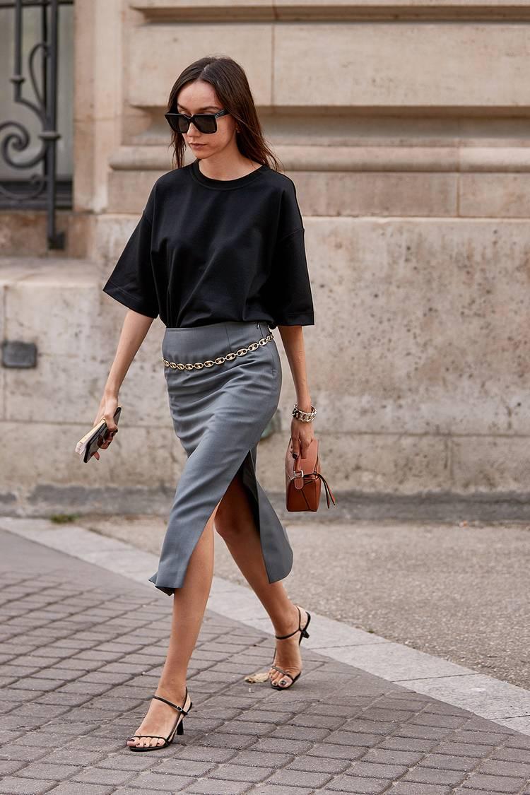 Девушка в серой юбке карандаш, черная футболка и босоножки с ремешками