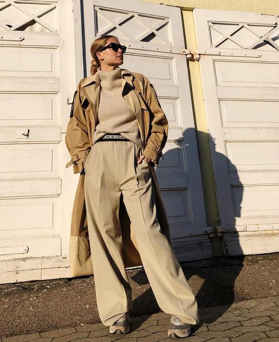 Девушка в широких брюках, бежевый свитер и классический тренч