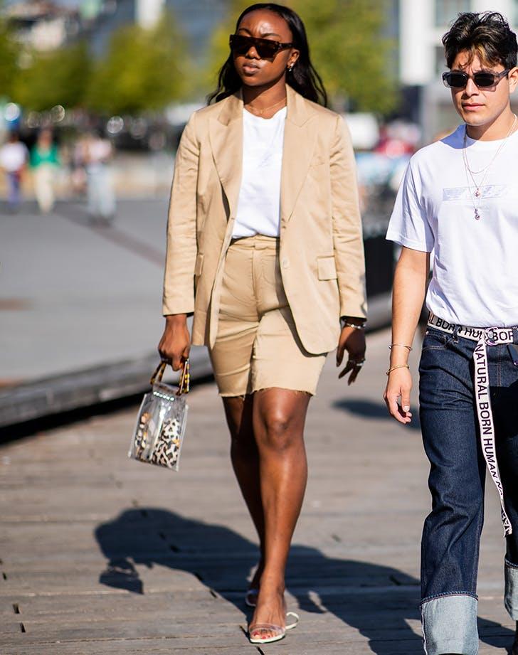 Девушка в шортах, блейзере, белой футболке и прозрачных босоножках