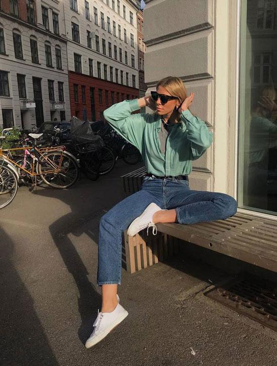 Девушка в синих джинсах, голубая рубашка и белые кеды