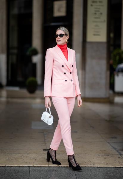Девушка в светло розовом брючном костюме, черная сумочка