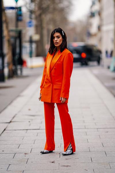 Девушка в ярком оранжевом брючном костюме и сапогах из змеиной кожи
