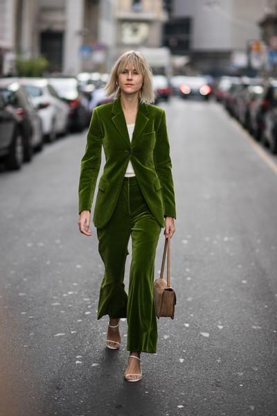 Девушка в зеленом бархатном костюме, белые босоножки и бежевая сумочка