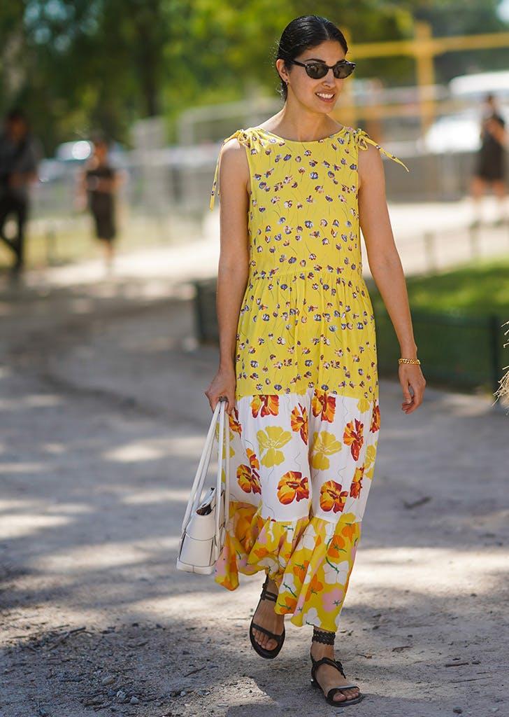 Девушка в желтом длинном сарафане и черных сандалиях с ремешками