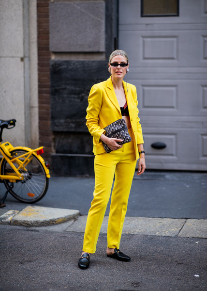 Девушка в желтом костюме, черные лоферы и сумочка