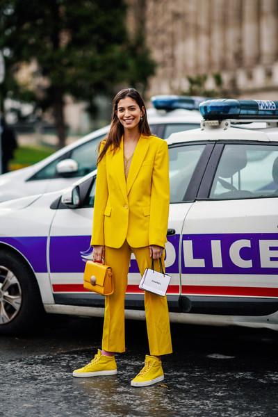 Девушка в желтом костюме с брюками, кроссовки и сумочка
