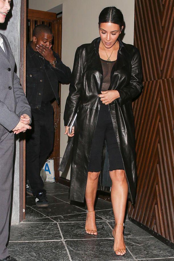 Ким Кардашян в черные джинсовых шортах и кожанном плаще