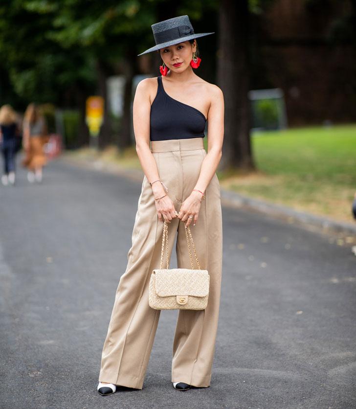 девушка в бежевых брюках, черной шляпе и асимметричном топе