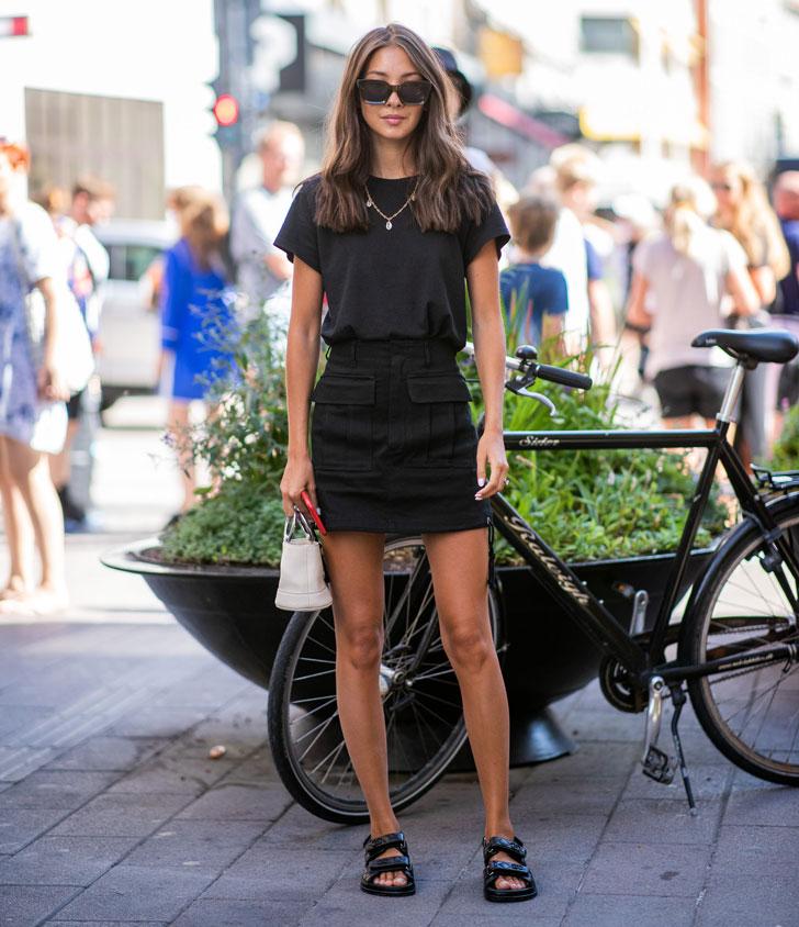 девушка в черной мини юбке, футболке и сандалиях