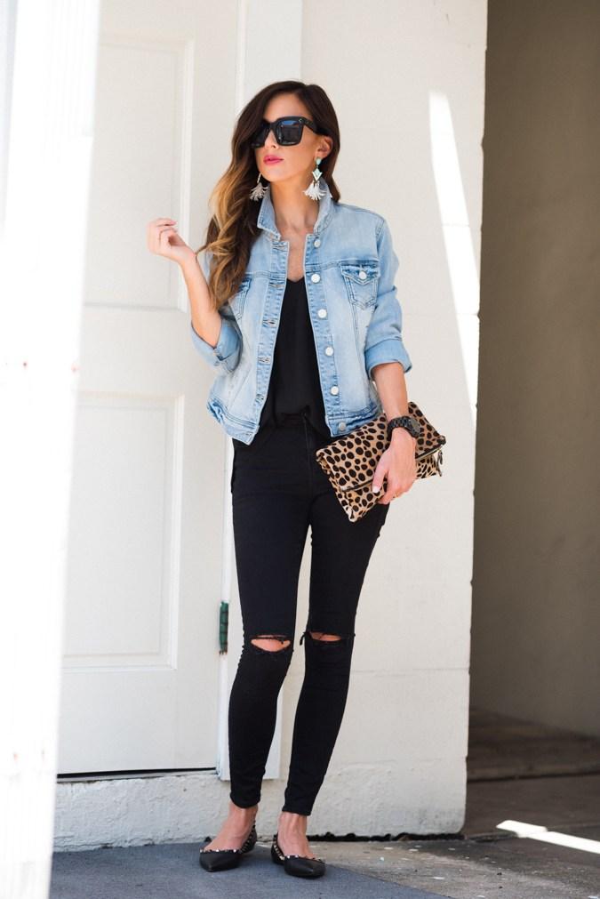 девушка в черных рванных джинсах, топ и джинсовая куртка