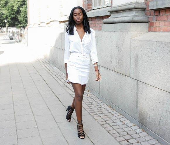 девушка в джинсовой мини юбке, белой рубашке и черных сандалиях