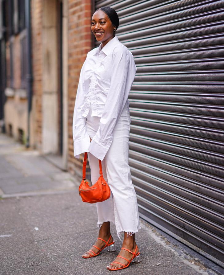 женщина в белых обрезанных джинсах, блузе с длинными руками и оранжевых босоножках