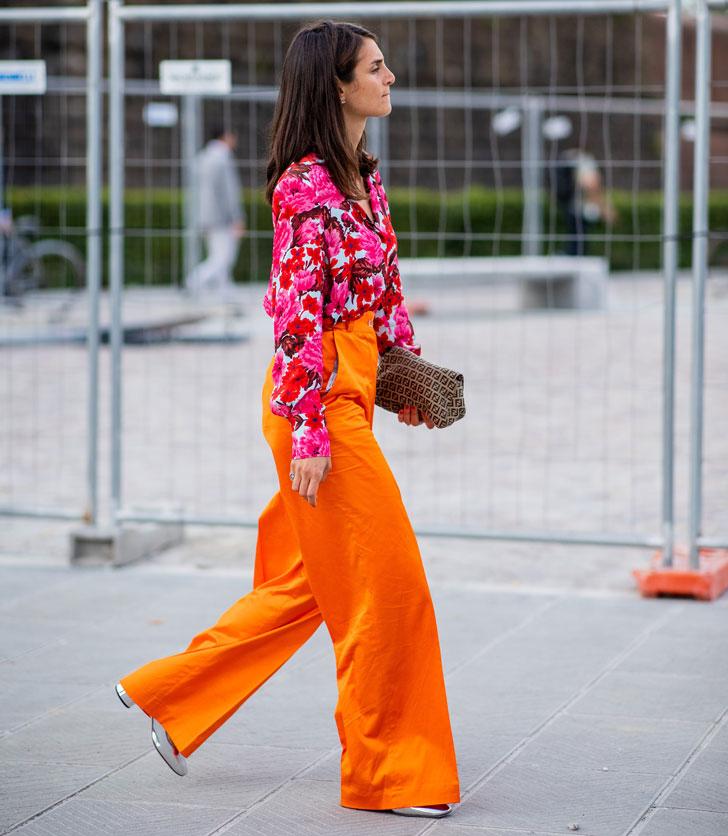 женщина в оранжевых брюках, блузе в цветочек и серебристой обуви