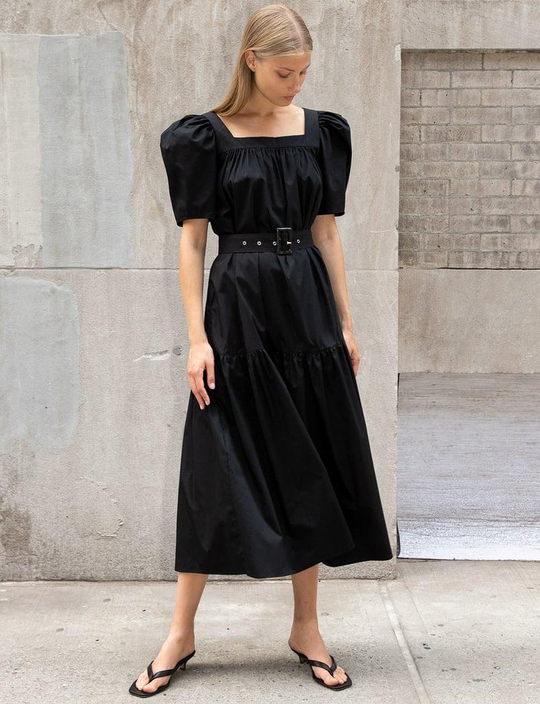 Девуша в черном романтичном платье миди с объемными рукавами и сандалии