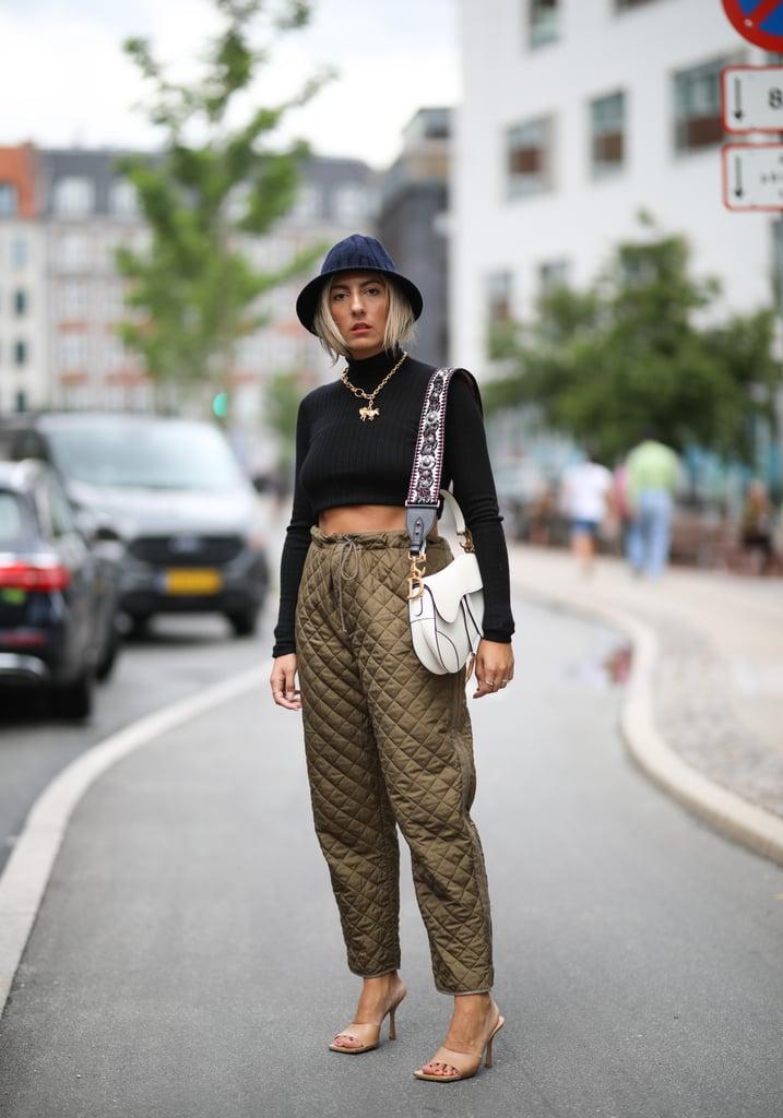Девушка коричневых брюках, укороченная черная водолазка, бежевые босоножки