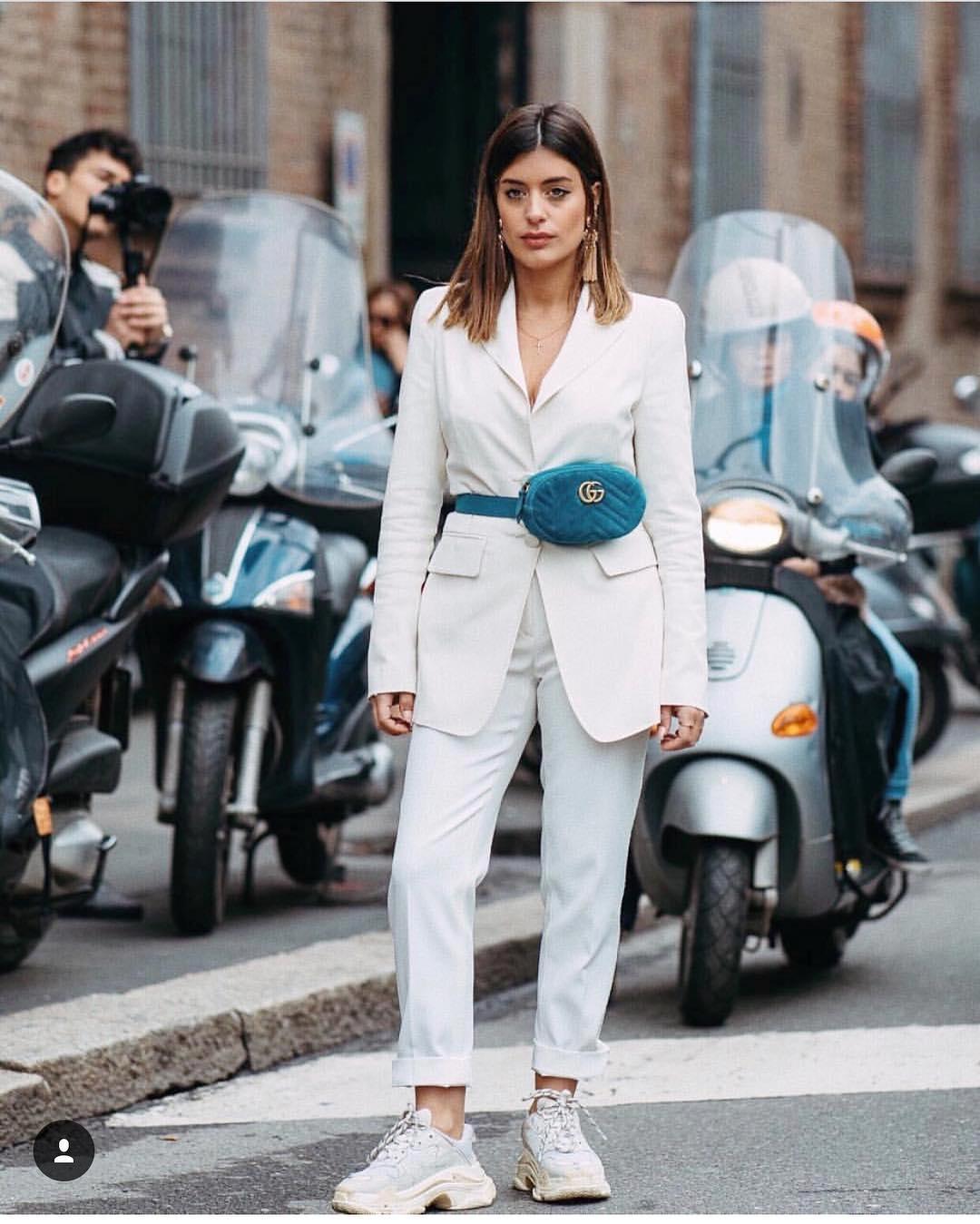 Девушка в белом брючном костюме, синяя поясная сумка и белые кроссовки