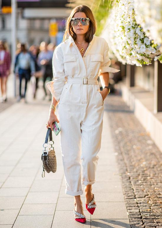Девушка в белом комбинезоне с поясом, красные туфли и сумочка