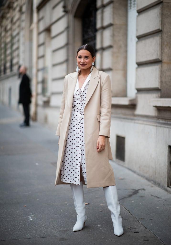 Девушка в белом платье миди в горох, бежевое пальто и сапоги