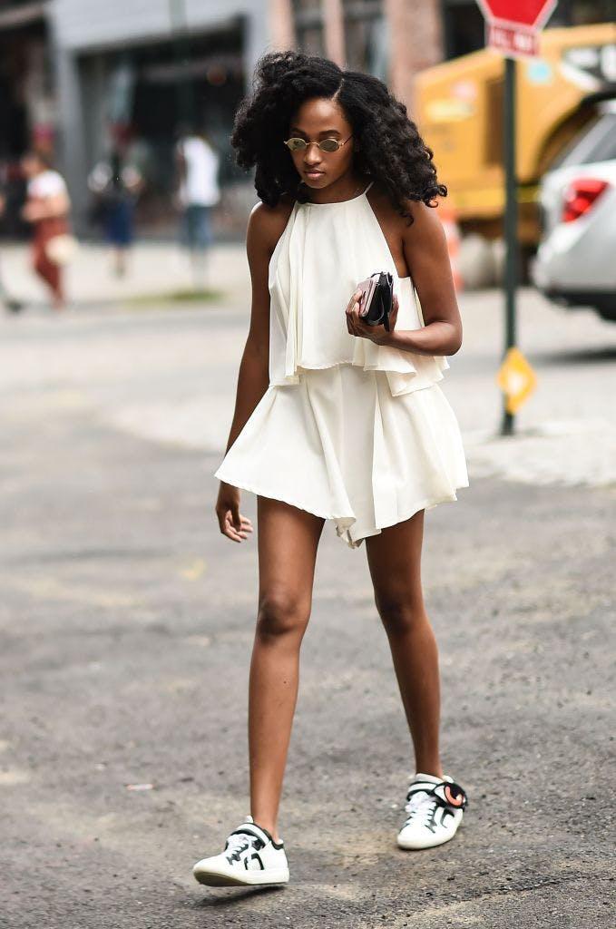 Девушка в белом просторном комбинезоне и кедах