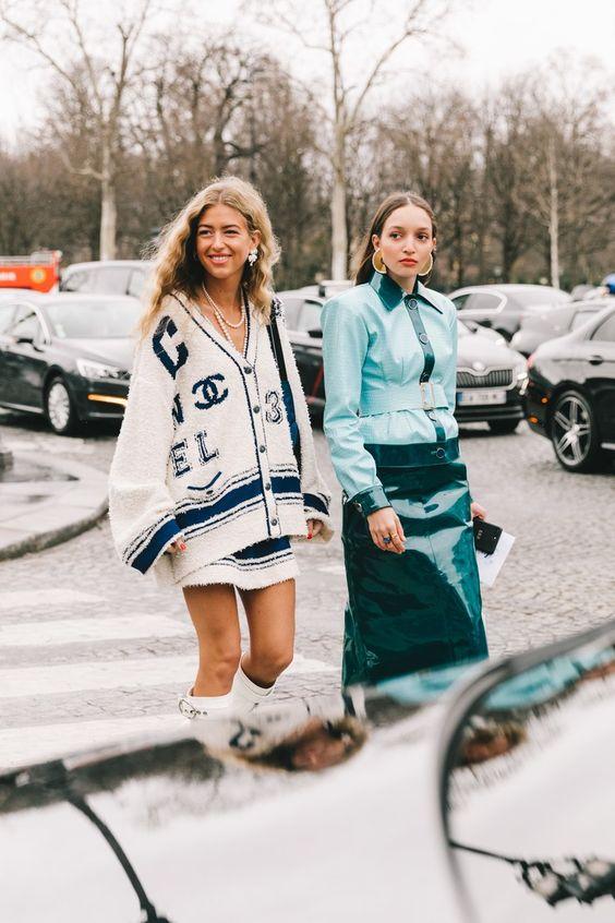 Девушка в белой мини юбке и кардигане оверсайз с логотипом