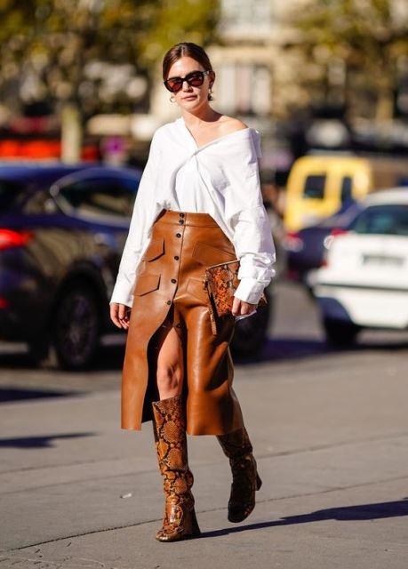 Девушка в белой рубашке коричневая кожаная юбка миди и сапоги из змеинной кожи