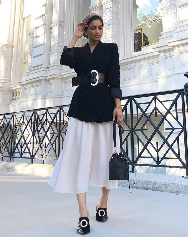 Девушка в белой юбке миди, черный блейзер с ремнем и туфли