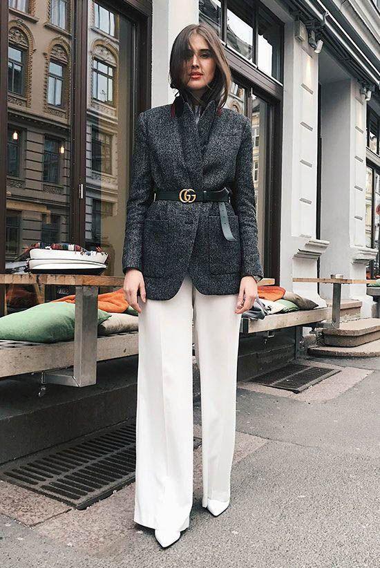 Девушка в белых брюках, серый блейзер с ремнем и белые туфли