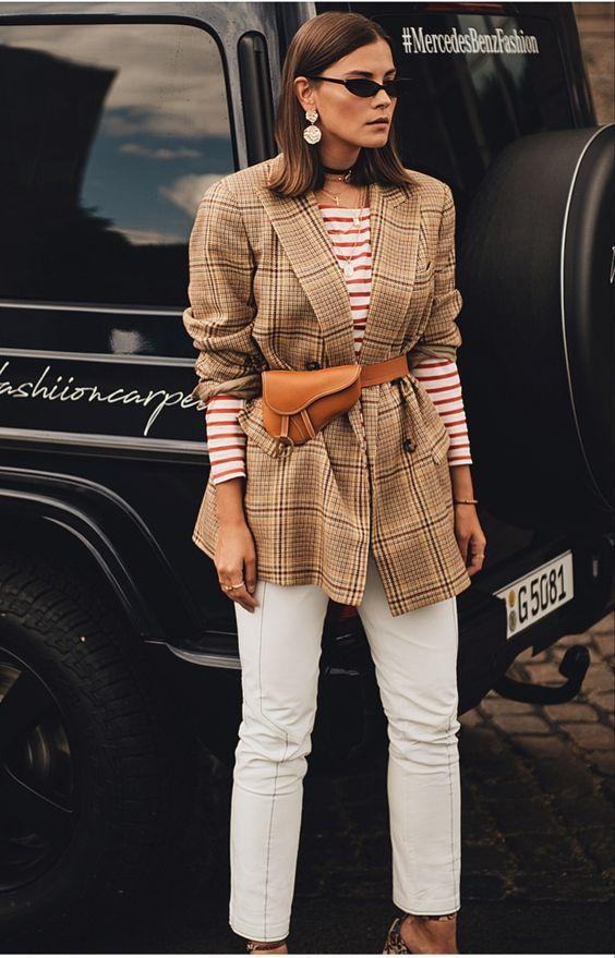 Девушка в белых джинсах, коричневый пиджак в клетку и поясная сумка