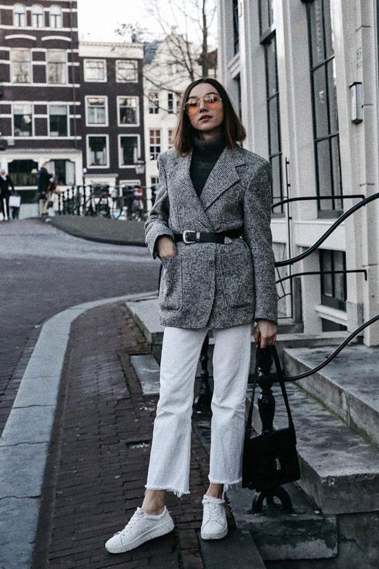 Девушка в белых укороченных джинсах, серый блейзер с ремнем и белые кеды