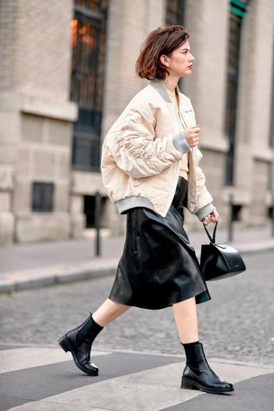 Девушка в бежевом бомбере, кожаная юбка по колено и черные ботинки
