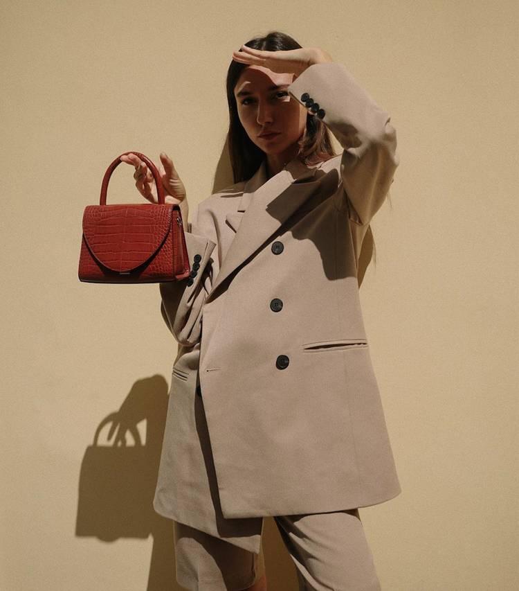 Девушка в бежевом костюме, красная жесткая сумка