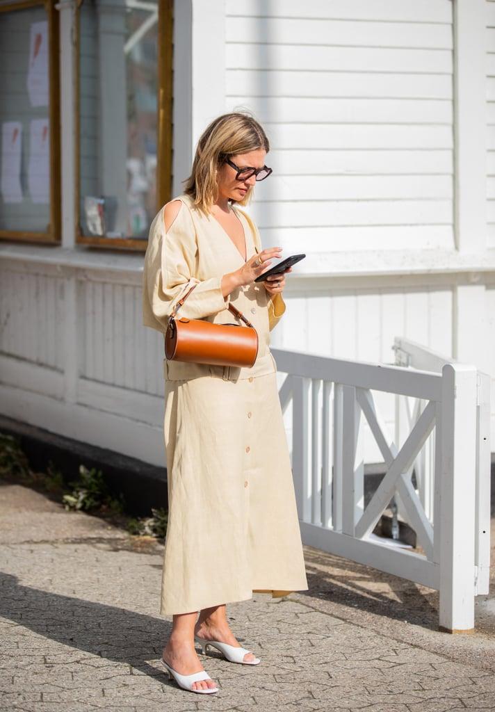 Девушка в бежевом платье макси и белые туфли на низком каблуке