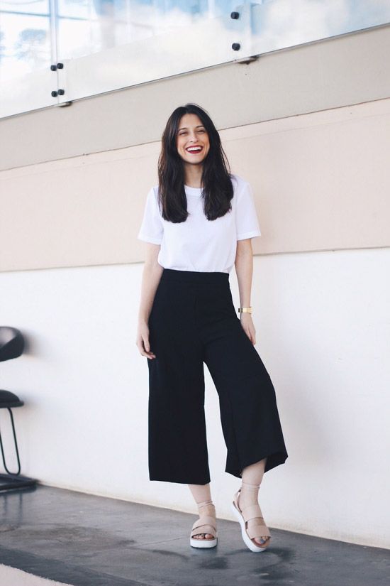 Девушка в брюках кюлотах, белая футболка и сандалии
