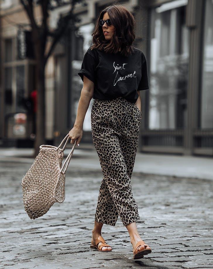 Девушка в брюках с леопардовым принтом, черная футболка и сланцы