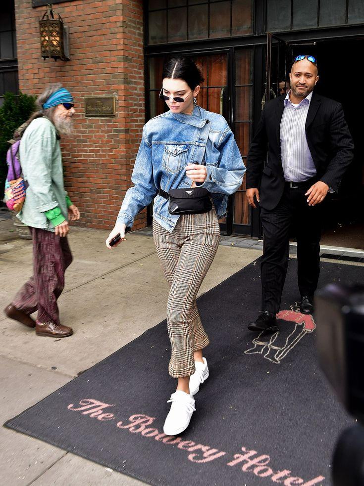 Девушка в брюках в клетку, джинсовка, белые кеды и черная поясная сумка