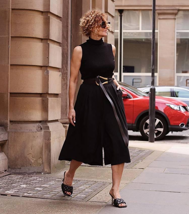 Девушка в черном комбинезоне с длинным ремнем и босоножки