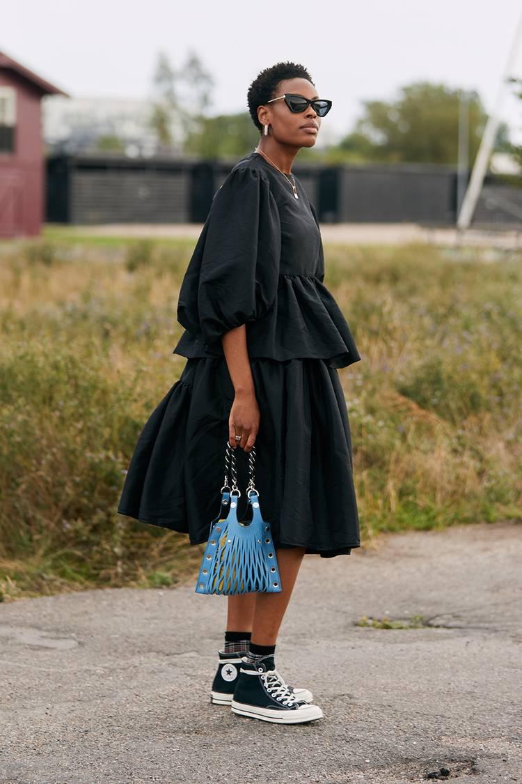Девушка в черном платье миди, кеды и голубая сумочка