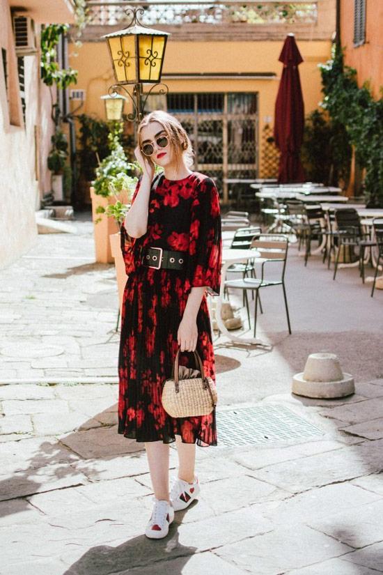 Девушка в черном платье с красными цветами и ремнем, белые кеды и соломенная сумка
