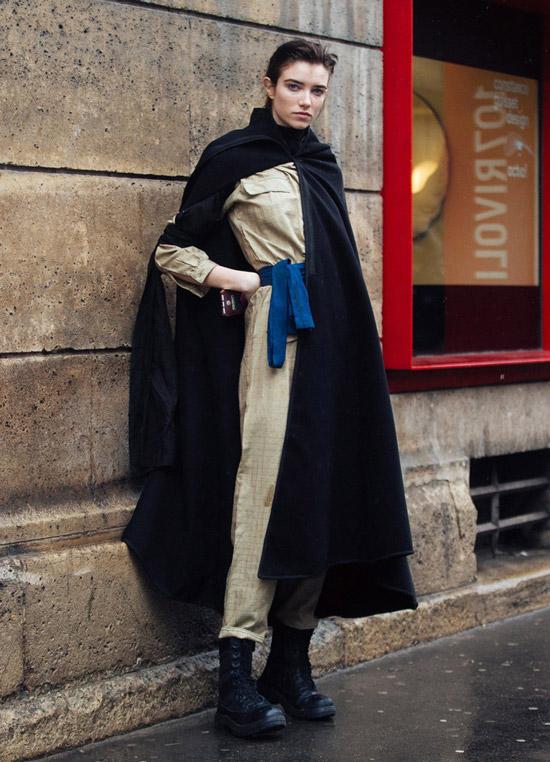 Девушка в черной накидке пальто, улитарный комбинезон и ботинки