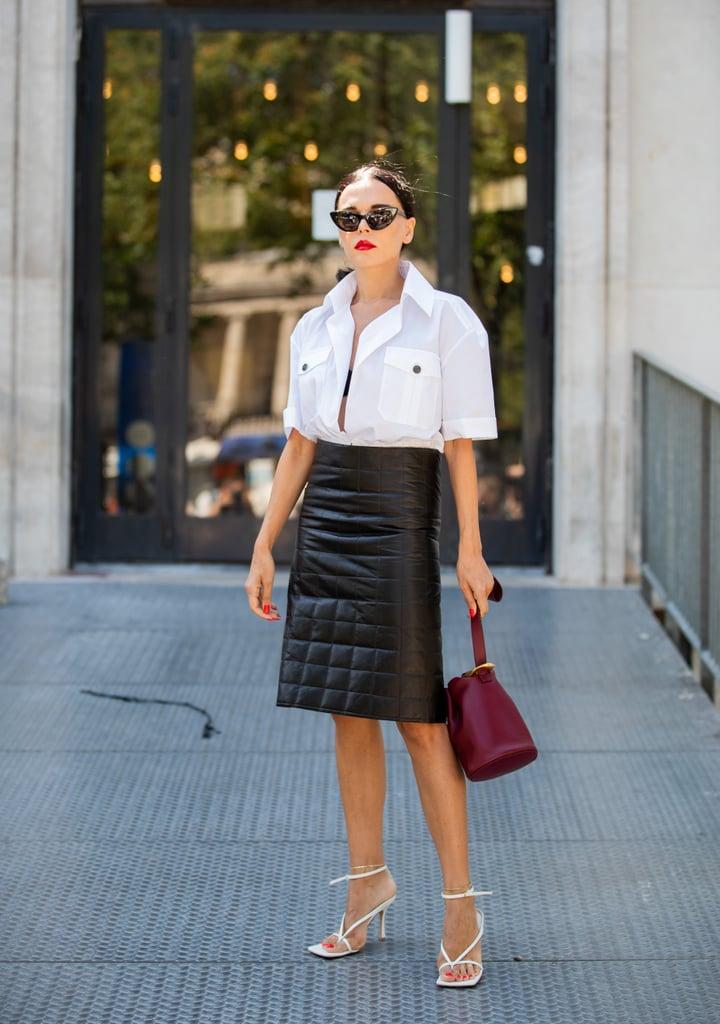 Девушка в черной юбке миди, белая рубашка и белые босоножки
