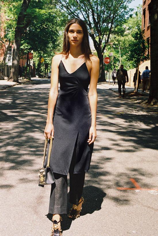 Девушка в черных брюках и платье на тонких лямках