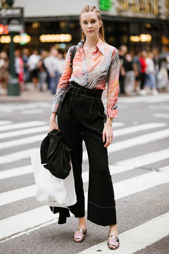 Девушка в черных брюках клеш, блузка и сандалии