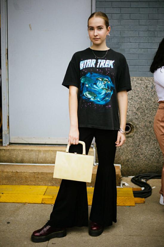Девушка в черных брюках клеш и футболка с принтом