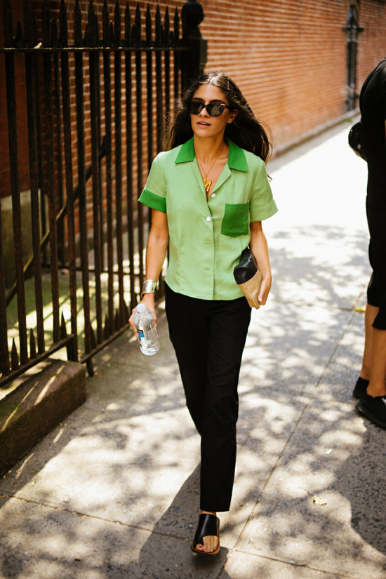 Девушка в черных брюках, зеленая рубашка и сандалии