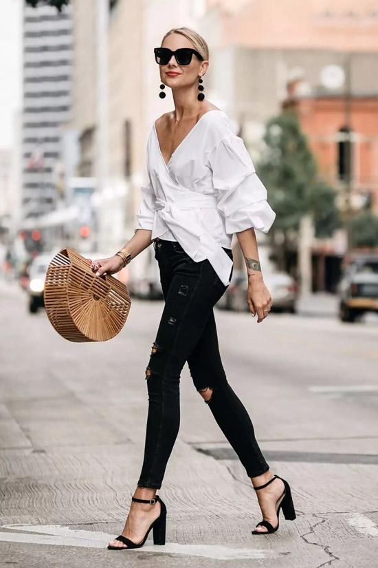 Девушка в черных джинсах скинни, белая блузка и босоножки