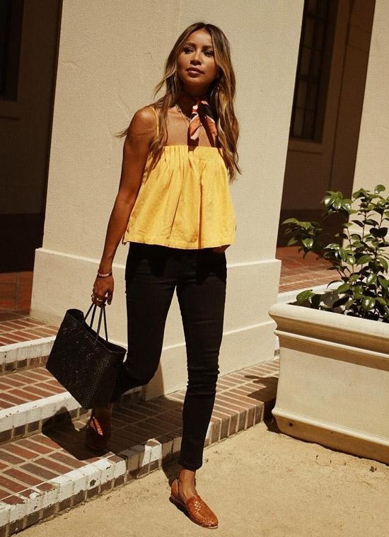 Девушка в черных джинсах скинни, желтый топ и коричневые балетки
