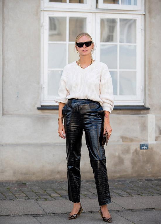 Девушка в черных кожаных штанах, белый джемпер и туфли