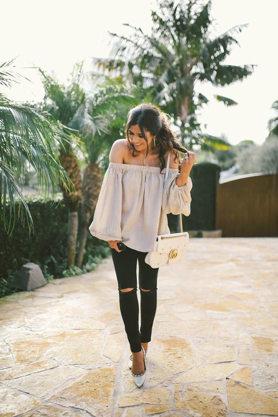 Девушка в черных рванных джинсах, свободная блузка и белые туфли